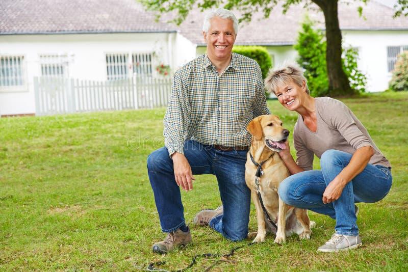 Deux personnes supérieures avec le chien devant la maison photos stock