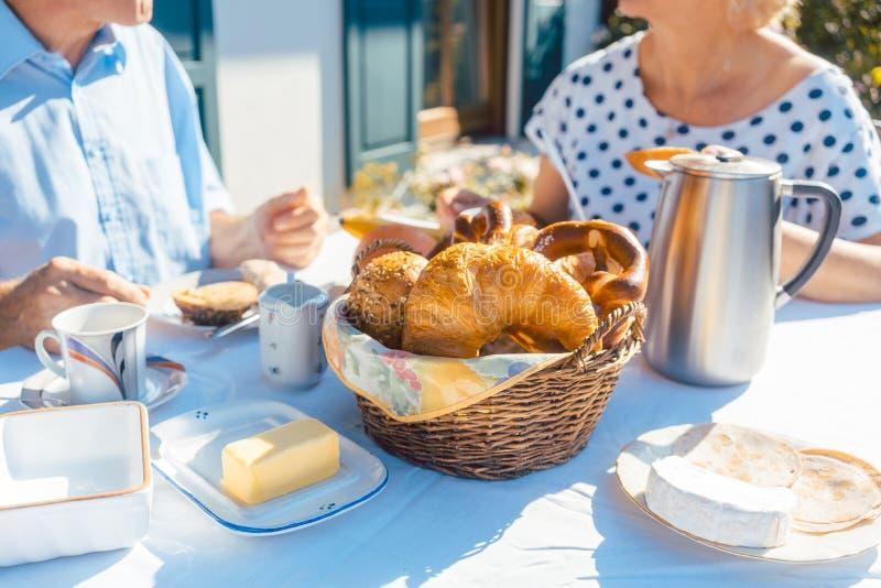 Deux personnes supérieures prenant le petit déjeuner avec le panier de pain sur la table dans le jardin d'été images libres de droits