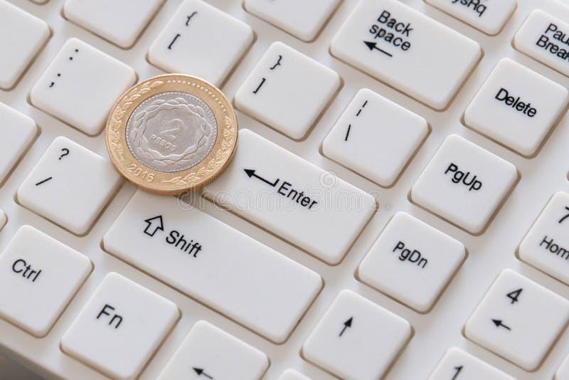Deux pesos d'en gros plan Une pièce en argent avec une frontière d'or se trouve sur le clavier avec l'alphabet latin Vente sur photo stock