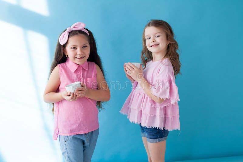 Deux petites filles boivent des amies de thé gentilles photographie stock