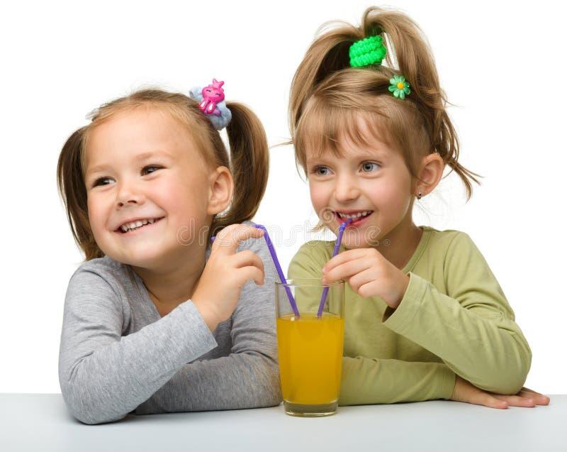 Deux petites filles boivent du jus d'orange photographie stock