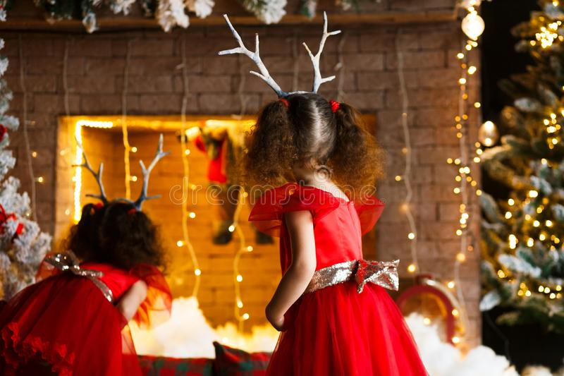 Deux petites filles bouclées regardant la cheminée de Noël près de b images stock