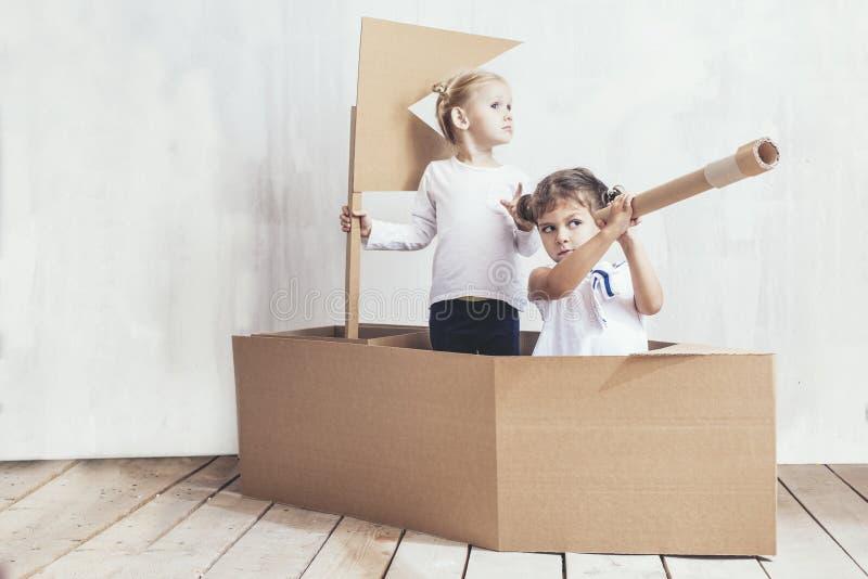 Deux petites filles d'enfants autoguident dans des capitaines d'un jeu de bateau de carton images libres de droits