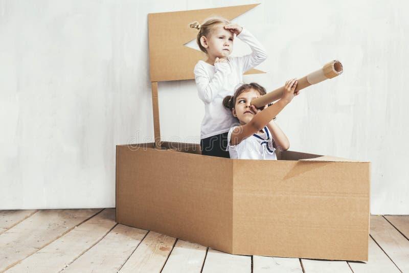 Deux petites filles d'enfants autoguident dans des capitaines d'un jeu de bateau de carton images stock