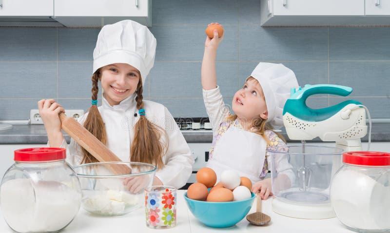 Deux petites filles dans l'uniforme de chef avec des ingrédients sur la table photo stock