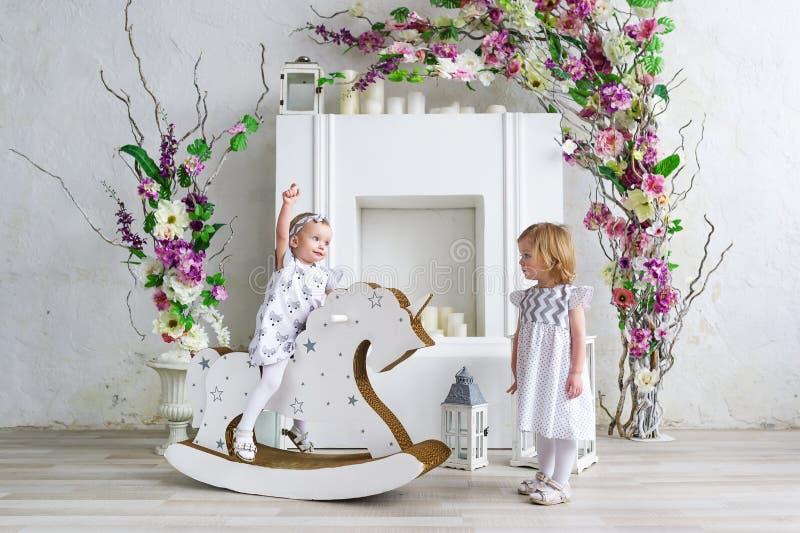 Deux petites filles de charme jouent dans la salle légère décorée des fleurs Bébé balançant sur un cheval en bois images libres de droits