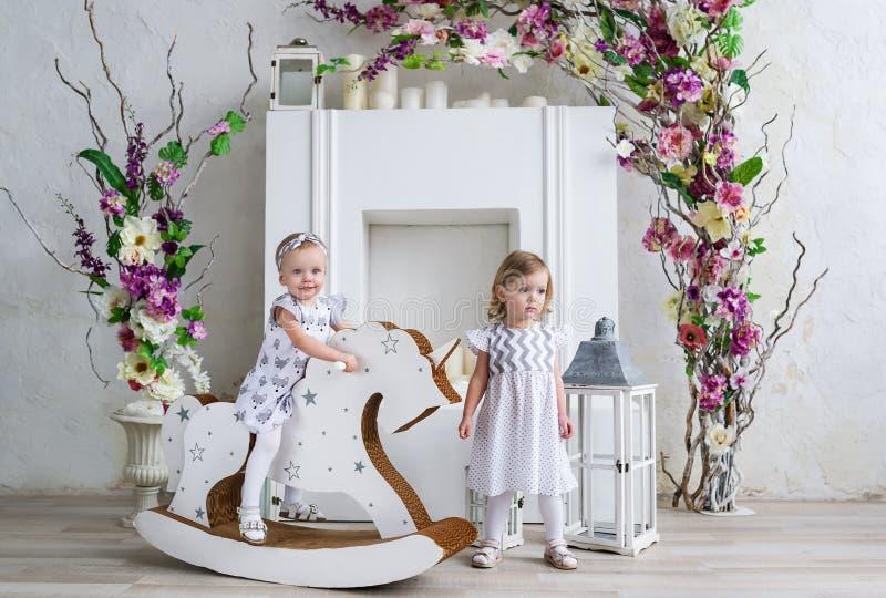 Deux petites filles de charme jouent dans la salle légère décorée des fleurs Bébé balançant sur un cheval en bois photographie stock