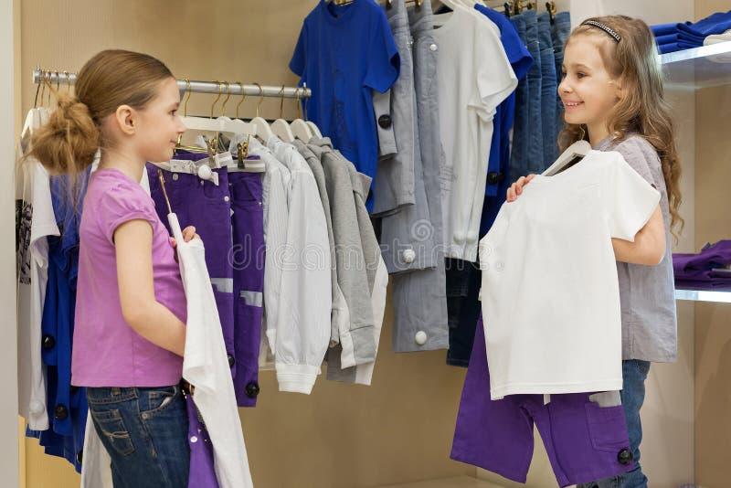 Deux petites filles de sourire essayant sur la même robe dans le magasin images libres de droits