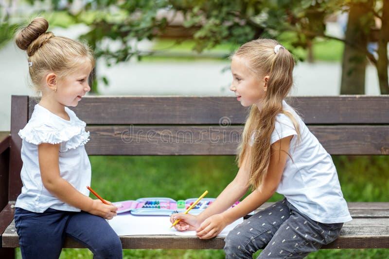 Deux petites filles dessinent en parc d'école Le concept de l'école, amitié, dessin, étude, passe-temps photo libre de droits