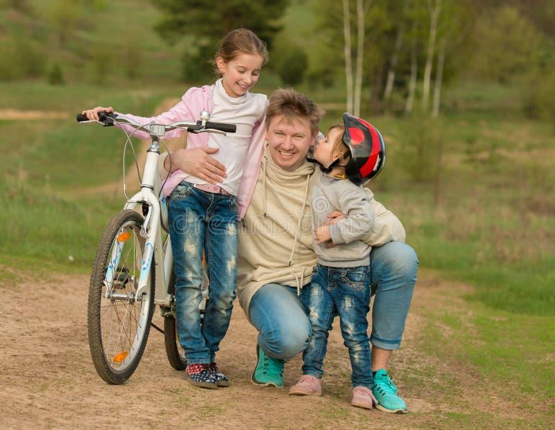 Deux petites filles embrassant le père sur une promenade dans la campagne photographie stock