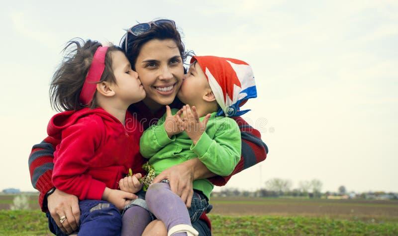 Deux petites filles embrassant leur mère dehors images libres de droits