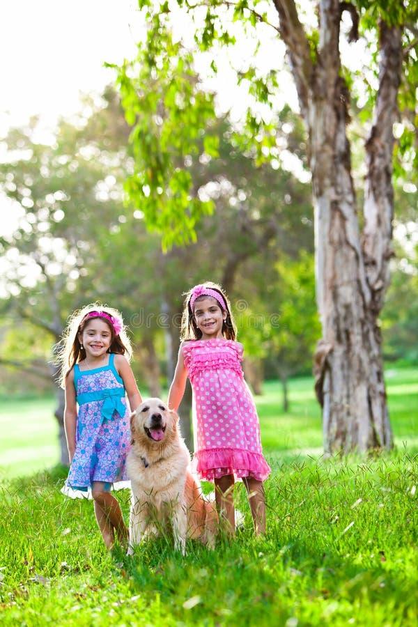 Deux petites filles heureuses et un chien d'arrêt d'or image stock