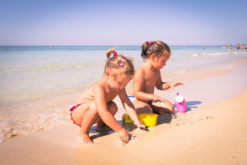 Deux petites filles jouant avec le sable près de la mer clair comme de l'eau de roche photos stock