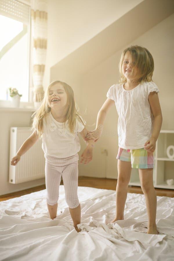 Deux petites filles jouant ensemble dans le lit images stock