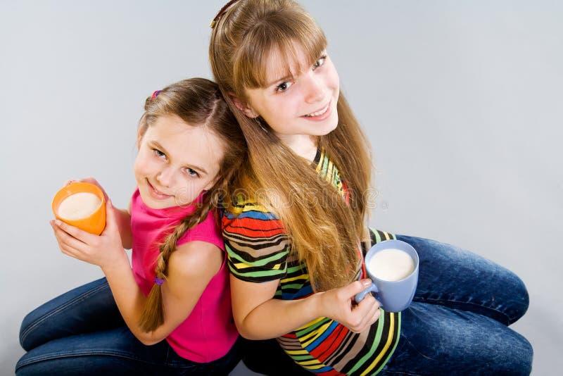 Deux petites filles mignonnes avec des tasses images stock