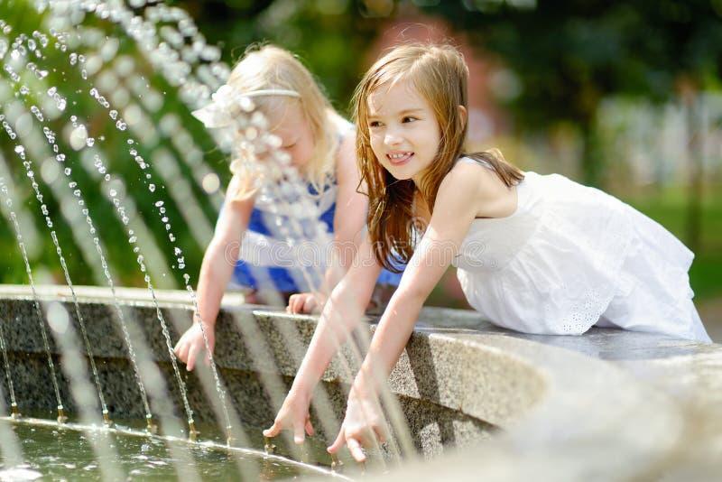 Deux petites filles mignonnes jouant avec une fontaine de ville photographie stock libre de droits