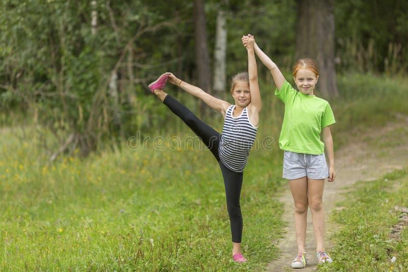 Deux petites filles mignonnes réchauffant dehors image stock