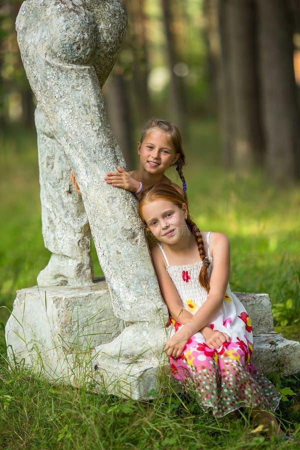 Deux petites filles posant près de la statue en parc photographie stock libre de droits
