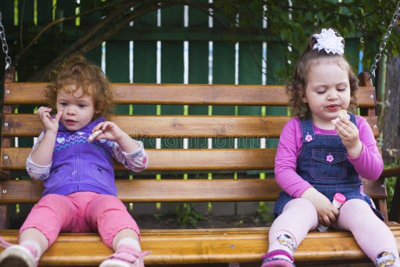 Deux petites filles s'asseyent sur un banc accrochant et mangent des biscuits photo stock