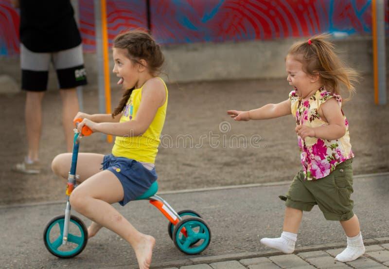 Deux petites filles se sont avec émotion disputées au-dessus d'un scooter images stock