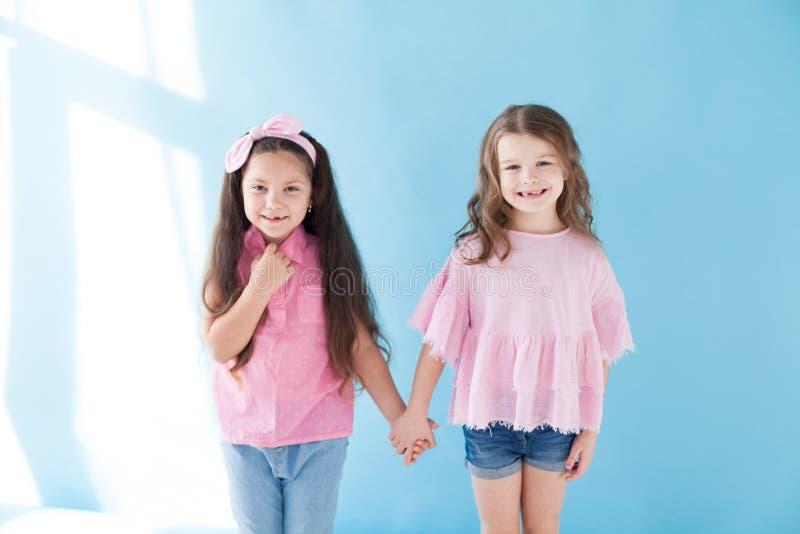 Deux petites filles sont des amies de soeurs dans une robe rose images libres de droits