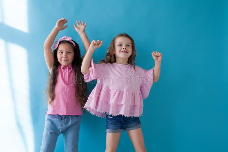 Deux petites filles sont des amies de soeurs dans une robe rose images stock