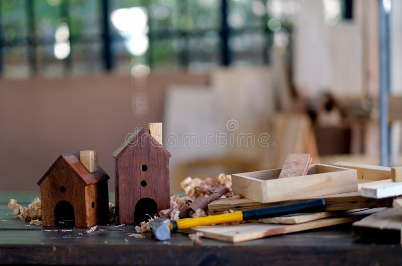 Deux petites maisons en bois ou boîtes d'oiseau sont mises sur la table parmi la pile en bois et tout autre équipement pour ouvre images stock