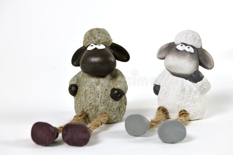 Deux petites poupées de moutons se reposant au sol photos libres de droits