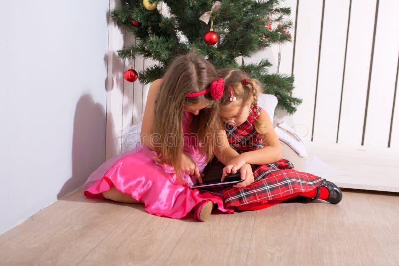 Deux petites soeurs à l'aide du PC de comprimé photos libres de droits
