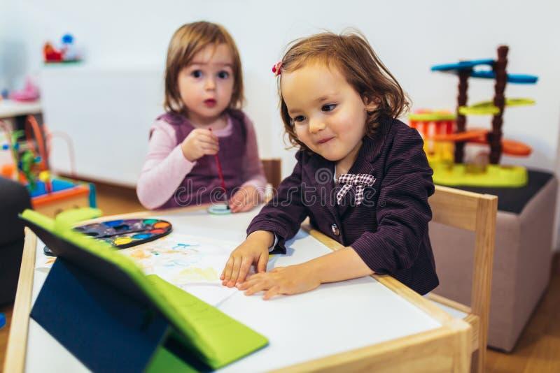 Deux petites soeurs adorables jouant avec un comprimé numérique à la maison photographie stock libre de droits