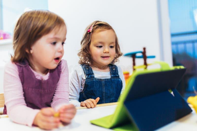 Deux petites soeurs adorables jouant avec un comprimé numérique à la maison image stock