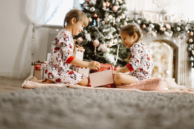 Deux petites soeurs heureuses dans des pyjamas s'asseyent sur le tapis et ouvrent les cadeaux de nouvelle année dans la salle co image stock
