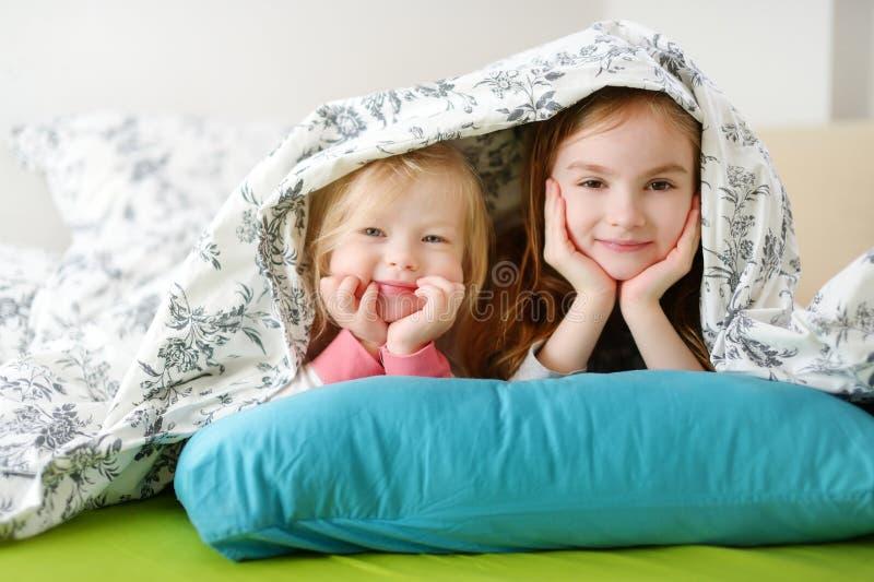 Deux petites soeurs jouant dans le lit image stock