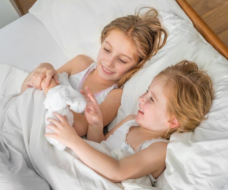 Deux petites soeurs jouant le jouet mou dans le lit photos stock