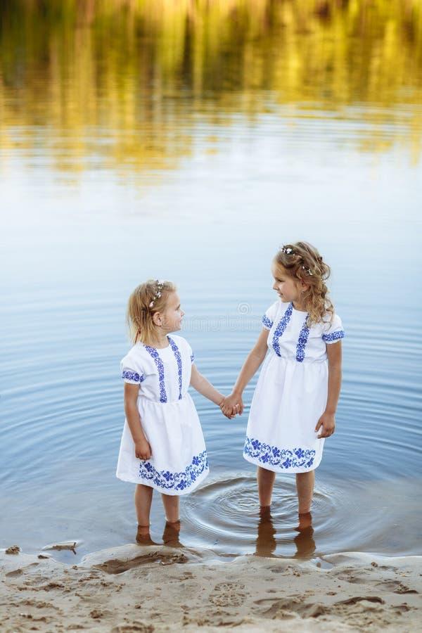 Deux petites soeurs riant et étreignant le jour chaud et ensoleillé d'été deux soeurs dans des robes blanches près de l'eau images libres de droits