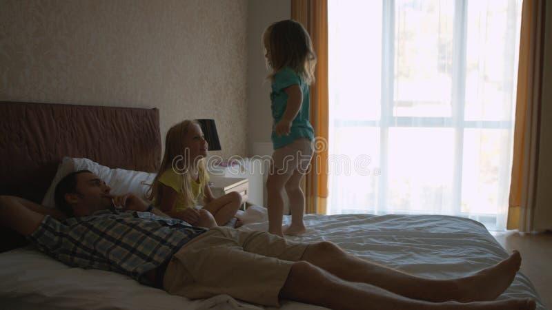 Deux petites soeurs sautant sur le lit et ayant l'amusement photographie stock
