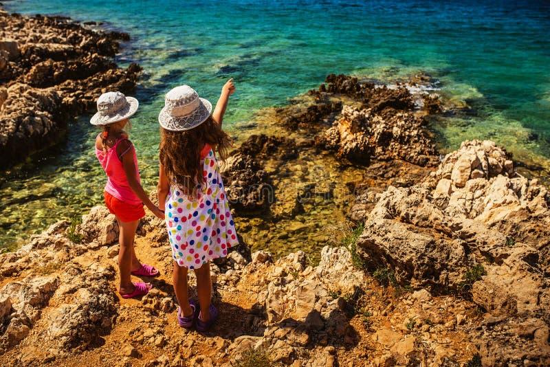 Deux petites soeurs sur les rivages rocheux de la mer image libre de droits