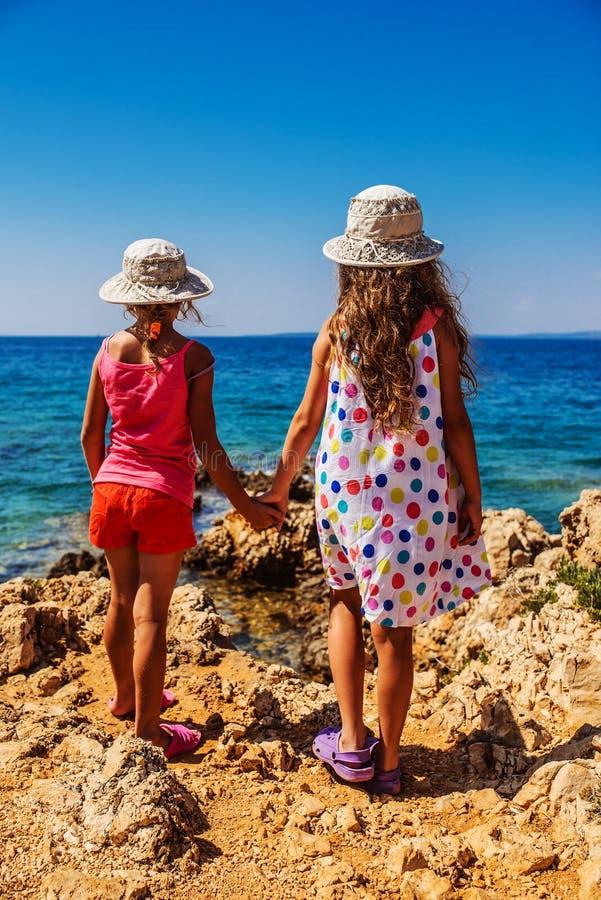 Deux petites soeurs sur les rivages rocheux de la mer image stock