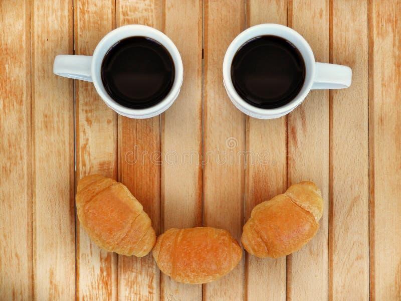 Deux petites tasses blanches de café et de trois croissants ressemblent au visage de sourire photo libre de droits