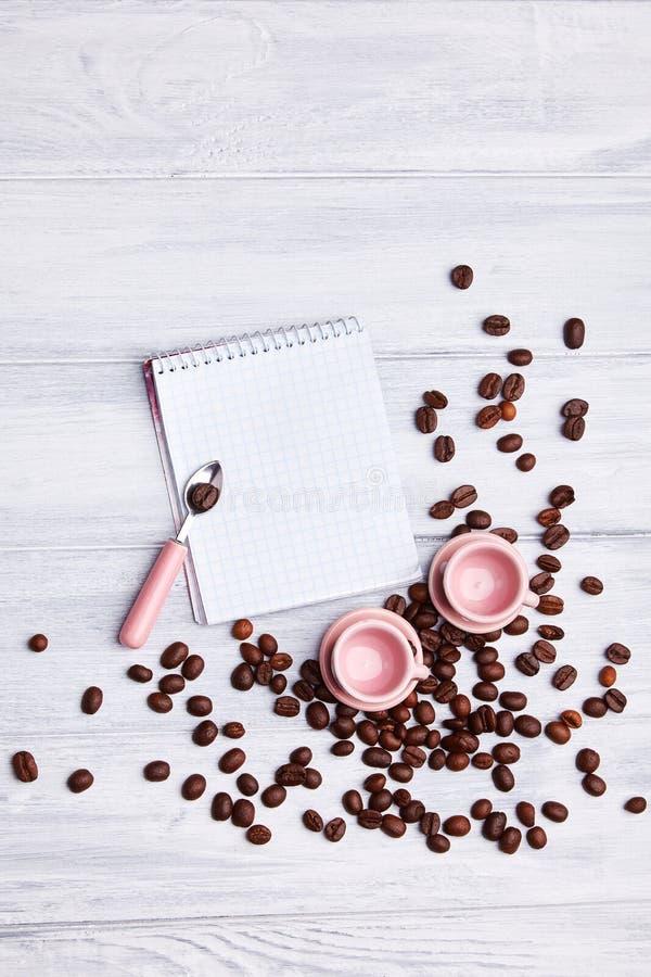 Deux petites tasses roses sur la table avec une cuillère, un bloc-notes et des grains de café dispersés sur un fond en bois blanc images libres de droits