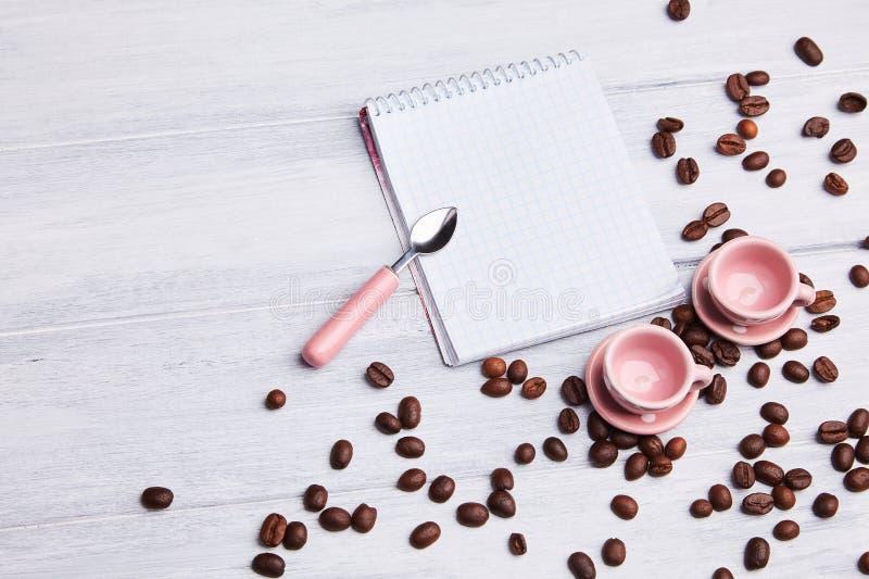 Deux petites tasses roses sur la table avec une cuillère, un bloc-notes et des grains de café dispersés sur un fond en bois blanc photographie stock libre de droits