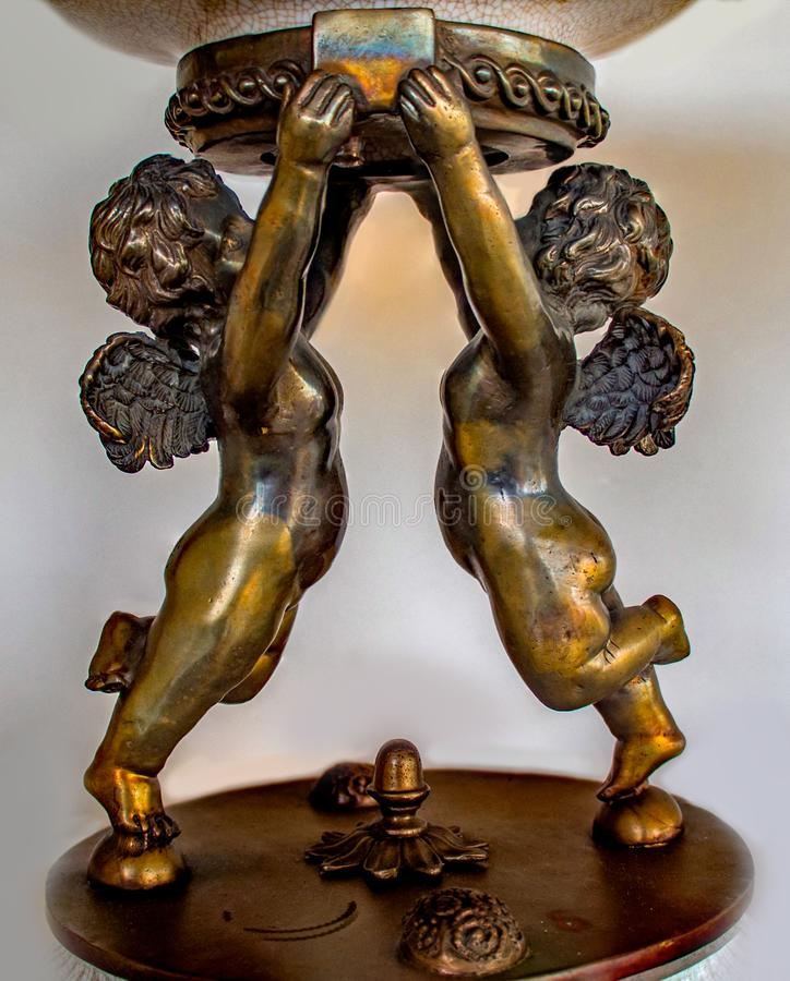Deux petits anges faits en laiton tenant une cuvette image libre de droits
