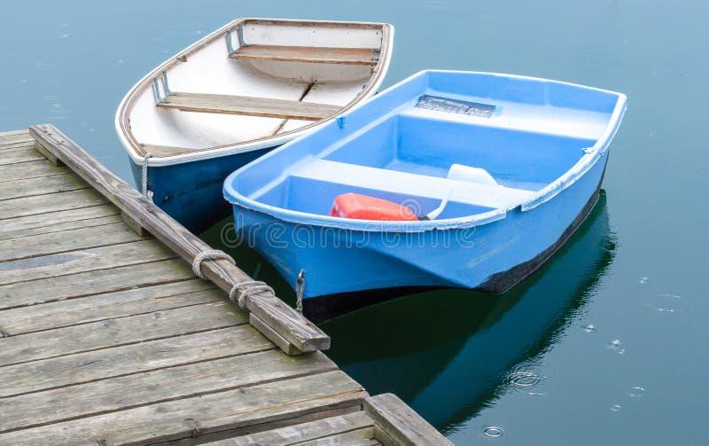 Deux petits bateaux à rames attachés à un dock en bois dans le Massachusetts images stock