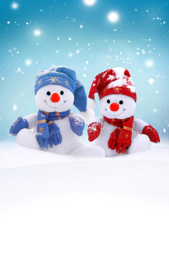 Deux petits bonhommes de neige la fille et le garçon dans les chapeaux et des écharpes sur la neige pendant l'hiver Fond avec un  image libre de droits