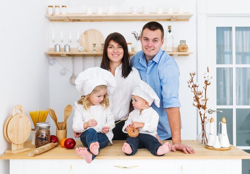 Deux petits chefs sittting sur la table dans la cuisine avec le père et la mère image libre de droits