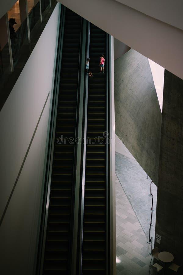 Deux petits enfants allant seul l'escalator photographie stock libre de droits