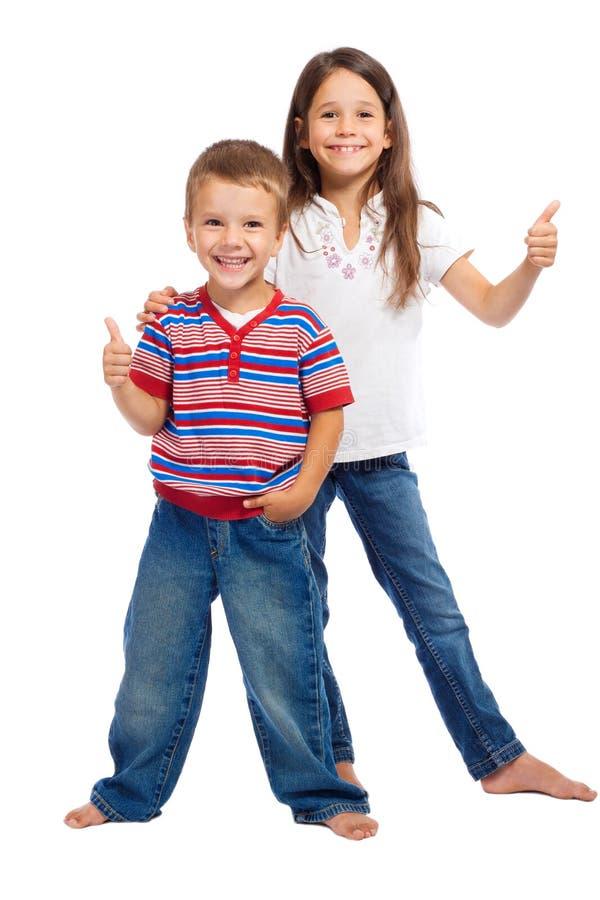 Deux petits enfants de sourire avec des pouces lèvent le signe image libre de droits