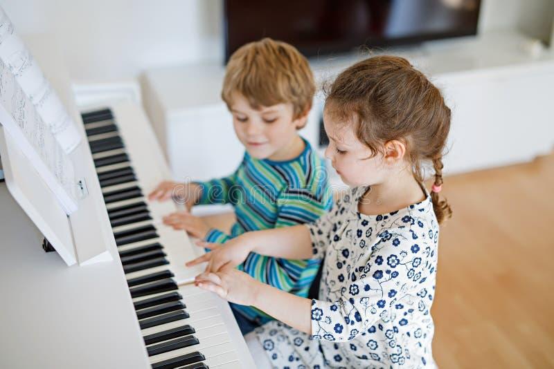 Deux petits enfants fille et garçon jouant le piano au salon ou à l'école de musique photographie stock