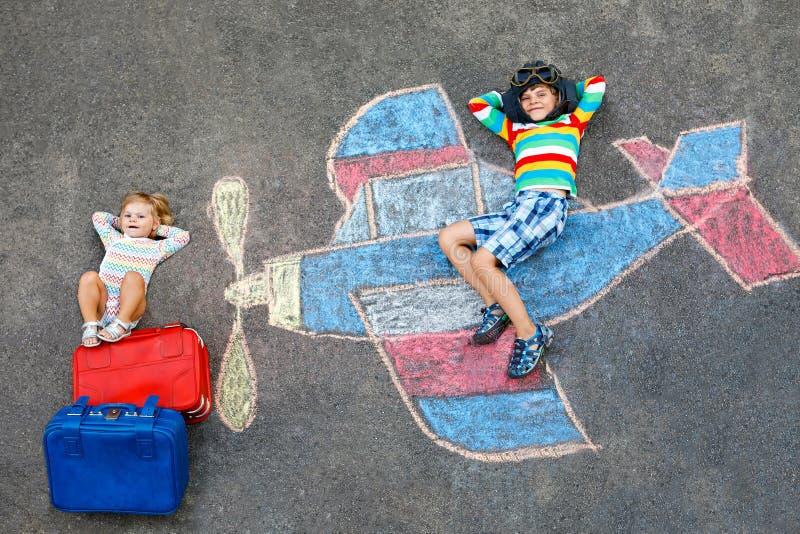 Deux petits enfants, garçon d'enfant et fille d'enfant en bas âge ayant l'amusement avec avec le dessin de photo d'avion avec les photo libre de droits