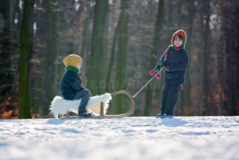 Deux petits enfants heureux, garçons, jouant dehors en parc neigeux photos stock